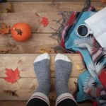 person in socks standing on a deck with fall leaves